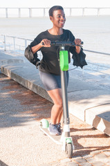 Happy Afro American millennial riding kick scooter. Cheerful black woman moving along seaside. Healthy lifestyle concept