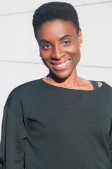 Happy black woman posing at camera outdoors. Young woman wearing casual blouse and looking at camera with wall in background. Woman portrait concept. Front view.