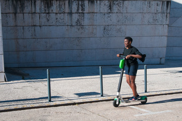 Smiling black woman enjoying riding electric scooter outdoors. Young woman wearing casual blouse and skirt with building in background. Modern transportation concept. Side view.