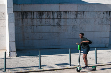 Positive black woman riding electric scooter outdoors. Young woman wearing casual blouse and skirt with building in background. Modern transportation concept.