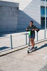Smiling black woman riding electric scooter outdoors. Young woman wearing casual blouse and skirt with building in background. Modern transportation concept.