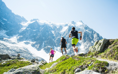 A group of trail runners running along a high mountain trail in the Alps under a clear blue sky. Fototapete