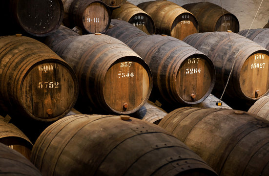 Wooden barrels with wine inside traditional winery with dark cellar for winemaking