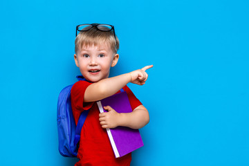Back to school First grade junior lifestyle. Small boy in red t-shirt. Close up studio photo portrait of smiling boy in glasses with schoolbag and book show somethind with his finger