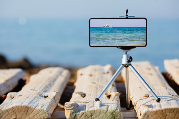Smartphone on tripod making photo and video of sea landscape