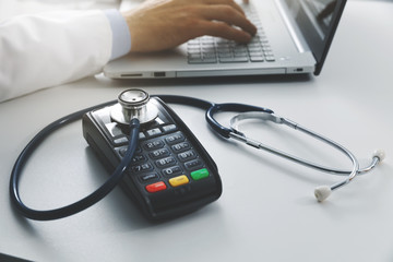 medical costs and health care expenses concept - payment terminal with stethoscope on the table in...