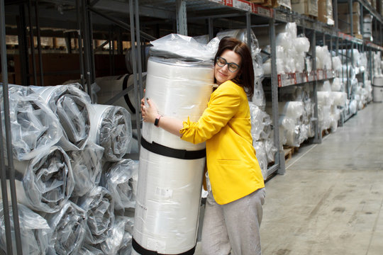 Girl with glasses takes a big and heavy mattress in the store. Wholesale and purchase. Self-service warehouse. Selection of products