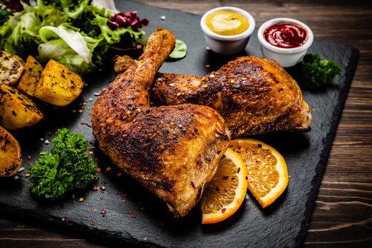 Roast chicken legs on black stone plate