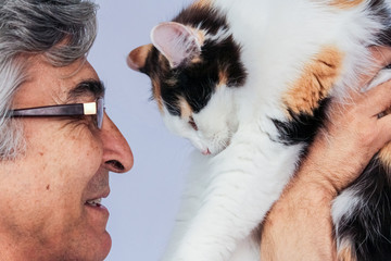 Happy adult man with spectacles holding a tricolor cat near his face