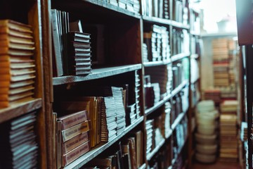selective focus of retro books on wooden shelves in library
