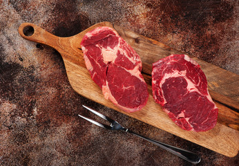 Wall Mural - Raw ribeye steaks on a wooden cutting board and meat fork on a brown concrete background, top view