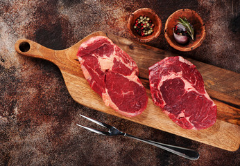 Wall Mural - Raw ribeye steaks, spices and meat fork on wooden cutting board on a brown concrete background, top view.