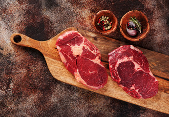 Wall Mural - Raw ribeye steaks and spices on wooden cutting board on a brown concrete background, top view.
