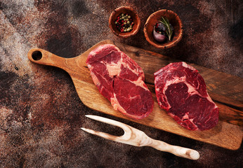 Wall Mural - Raw ribeye steaks, spices and meat fork on a brown concrete background, top view.