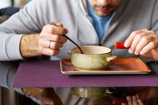 Caucasian male eating red soup