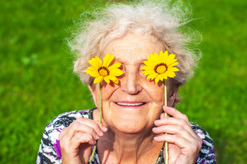 A cheerful grandmother looks at the flower look of yellow daisies. Women's health, skin care,...