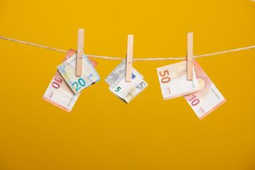 Billetes de Euro colgadois de una cuerda y cogidos por pinzas de madera de extender la ropa