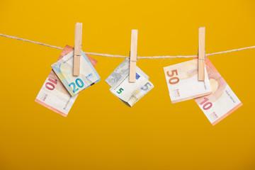 Billetes de Euro sobre fondo amarillo, colgados de una cuerda y sujetos por unas pinzas de madera de extender la ropa