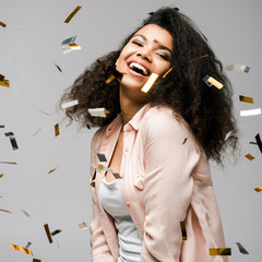 happy african american girl smiling near shiny confetti on grey