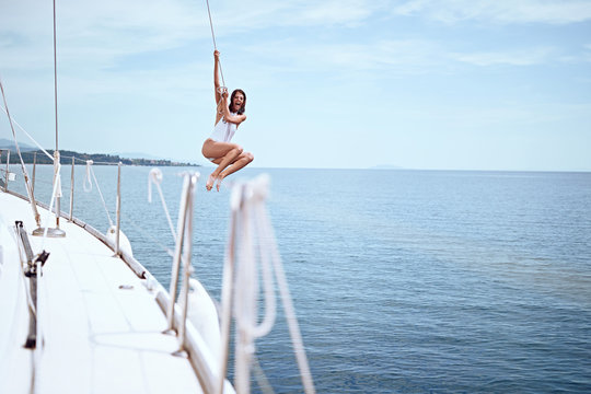 Girl jumping from sailing boat in sea. .