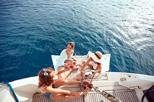 friend's girl having party on sailing boat and drinking wine top view.