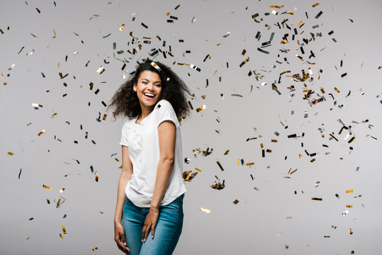 happy young african american woman smiling near shiny confetti while standing on grey