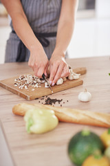 Dedicated Caucasian housewife in apron standing in kitchen and chopping mushrooms. On table are lots of vegetables. Cooking at home concept.