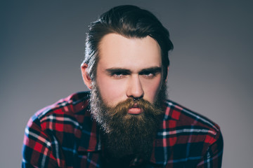 close up. portrait of a stern bearded man in a plaid shirt.