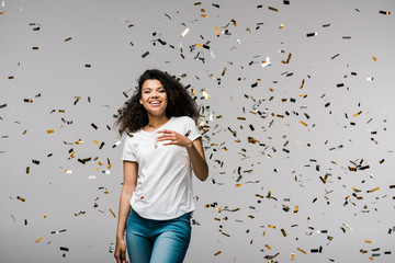 young african american woman smiling near shiny confetti while standing on grey
