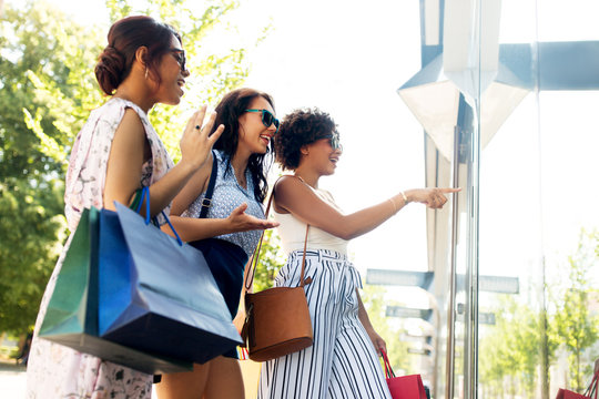 sale, consumerism and people concept - happy young women with shopping bags pointing finger to shop window in summer city