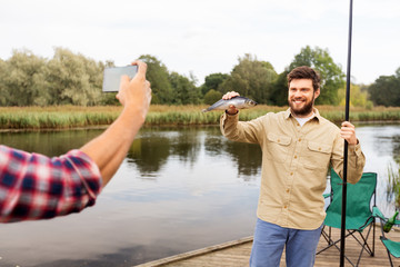 fishing, leisure and people concept - friend photographing fisherman with fish by smartphone at lake