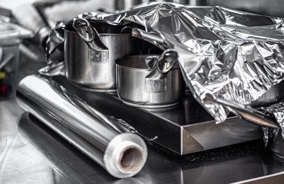 Steel pots on steel background under aluminium foil