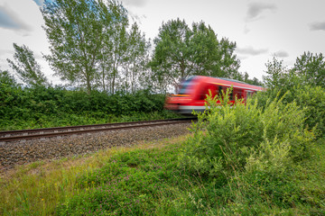 a red train races past a camera