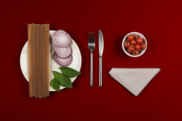 Ingredients for pasta recipe with white plate napkin & knife & fork