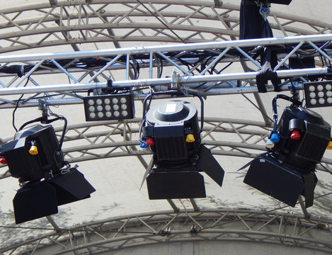 Black spotlights on a metal scaffold above the stage for illumination