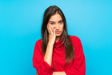 Young woman with red sweater over isolated blue background unhappy and frustrated