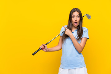 Young golfer woman over isolated yellow wall surprised and pointing side