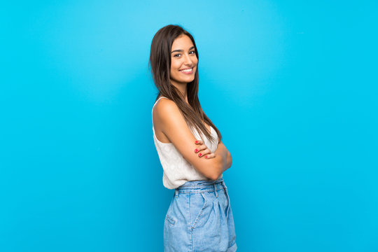 Young woman over isolated blue background with arms crossed and happy