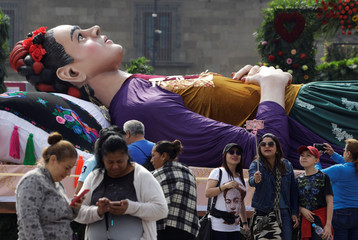 People take a selfie next to a large figure of Mexican artist Frida Kahlo lying on a bed during the exhibition 'Los Colores de Frida Kahlo' at Zocalo Square in Mexico City