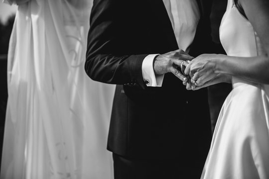 A bride and a groom are putting the rings on each others fingers. Black and white image.
