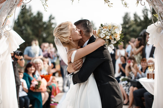 A bride and a groom are hugging in front of the guests. They are very happy.