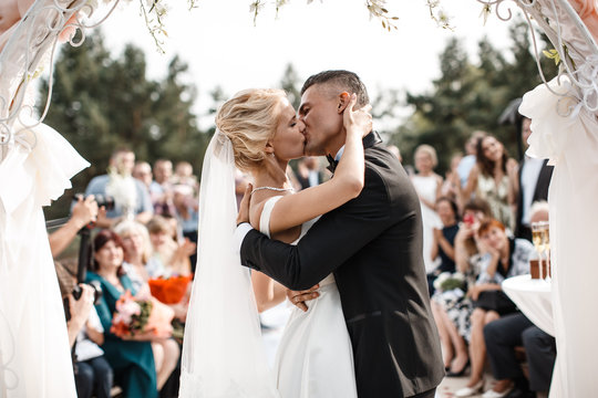 A bride and a groom are kissing in front of the guests.