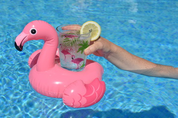 hand holding a drink in a pink flamingo inflatable drinks holder