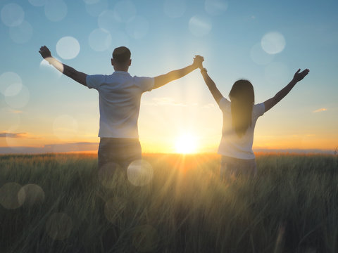 Young couple feeling free in a beautiful natural setting, in what field at sunset