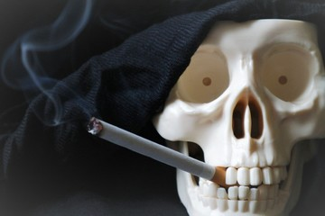 Skeleton skull with a lighted cigarette in her mouth. Harmfulness od smoking concept.