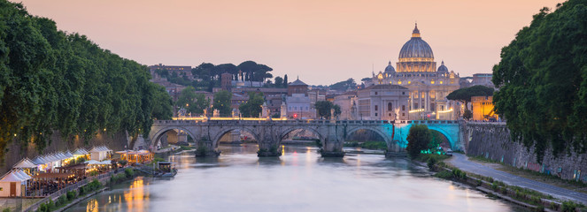 panorama of bridge and Cathedral of Saint Peter in sunset time in Rome in Italy