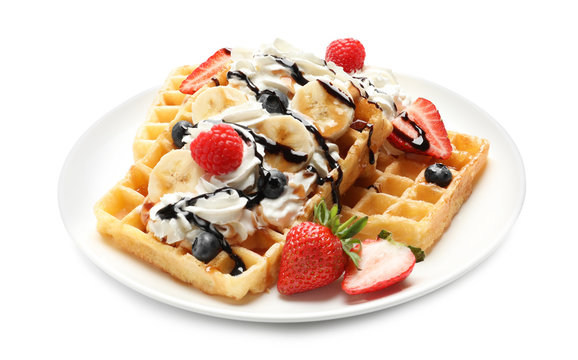 Plate with yummy waffles, whipped cream and berries on white background