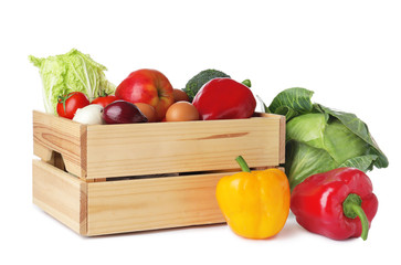 Wooden crate full of fresh products on white background