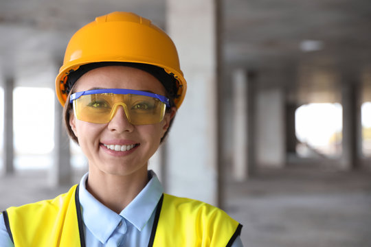 Professional engineer in safety equipment at construction site, space for text