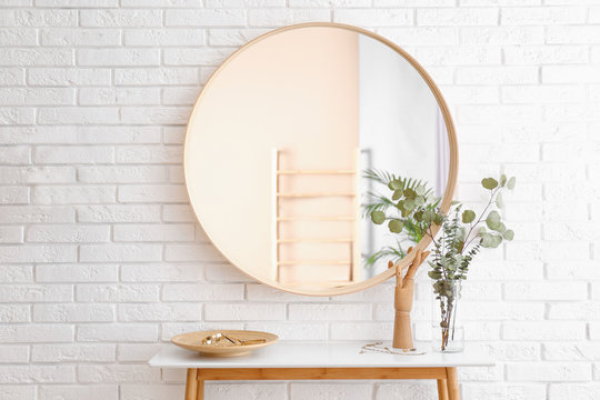 Big round mirror, table with jewelry and decor near brick wall in hallway interior